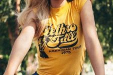 a retro look with a printed yellow t-shirt, blue denim shorts and sheer pink sunglasses