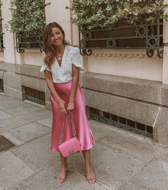 a romantic outfit with a white lace shirt, a pink satin midi, nude strappy sandals and a pink bag