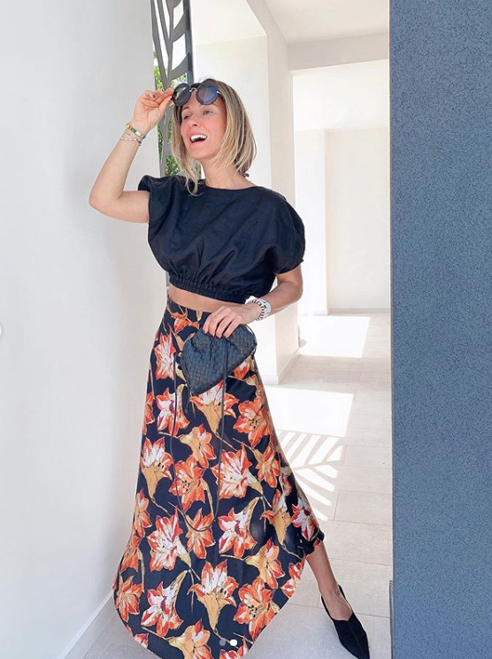 a sexy look with a black crop top with puff sleeves and a dark asymmetrical floral skirt, black mules and a bag