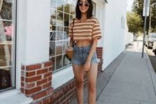 a sporty outfit with a striped crop top, blue denim shorts, white sneakers and a crossbody