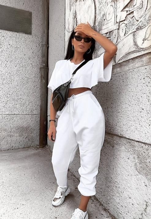 a sporty outfit with a white crop top, joggers, trainers and a black waist bag for summer