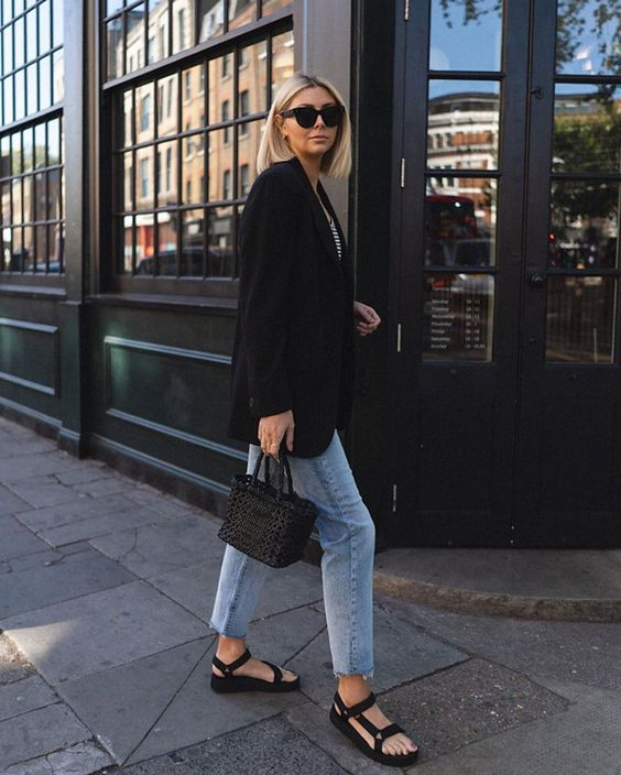 a striped top, a black blazer, blue jeans, black sporty sandals, a black woven bag for a casual outfit