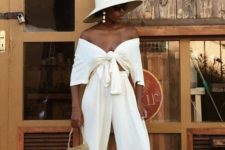 a stylish vacation look with a white off the shoulder tied crop top and matching pants, black slippers and a hat
