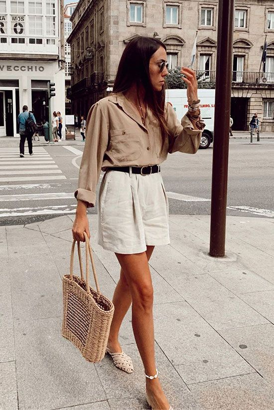 a tan shirt with long sleeves and pockets, white high waisted shorts, woven mules and a wicker bag
