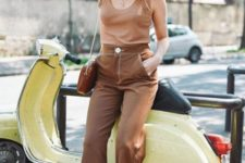 a tan top, brown cropped pants, brown lace up heels and a wide-brimmed hat plus a brown bag