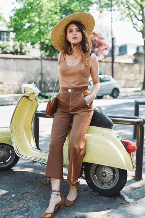 a tan top, brown cropped pants, brown lace up heels and a wide brimmed hat plus a brown bag