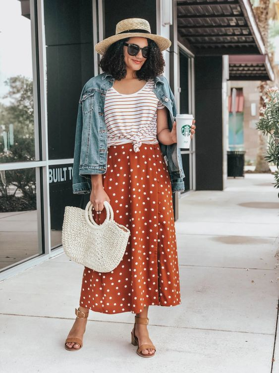 a trendy summer look with a striped tied up tee, a rust polka dot midi, tan heels and a blue denim jacket