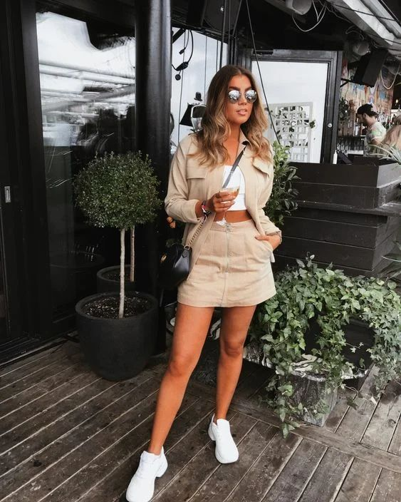 a white bra crop top, a tan mini skirt and a matching jacket, white trainers and a black bag