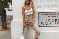 a white bra crop top, tan paper bag pants, white trainers and a white bag