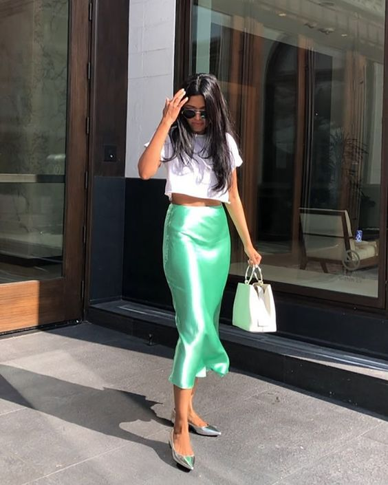 a white crop top, a neon green satin midi, silver slingbacks and a white bag