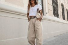 a white crop top, tan baggy jeans, neutral trainers and a fabric bag compose a comfy outfit