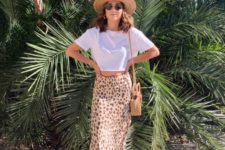 a white cropped tee, a leopard print satin midi, white sandals, a hat and a wicker bag