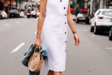 a white linen knee dress with buttons, tan minimalist heels, a wicker round bag and a denim jacket
