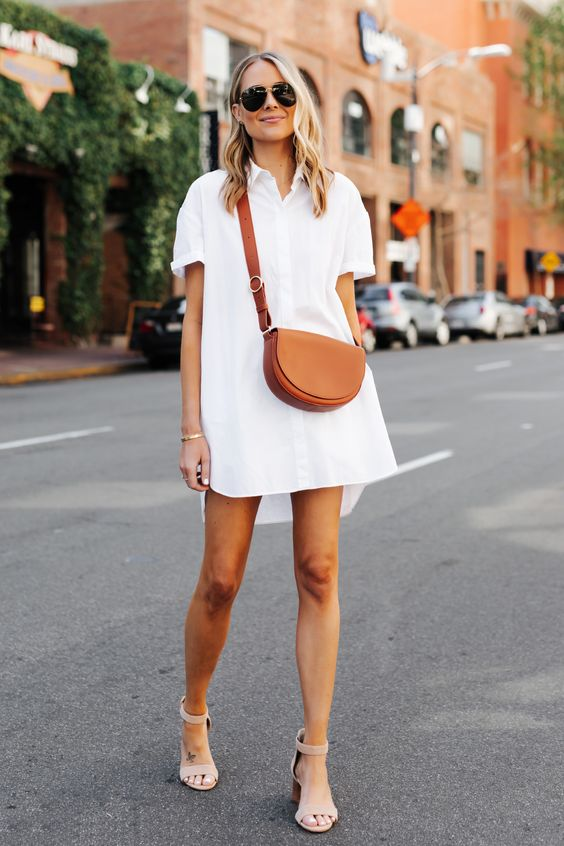 a white mini shirtdress, blush ankle strap shoes and a brown saddle bag for every day