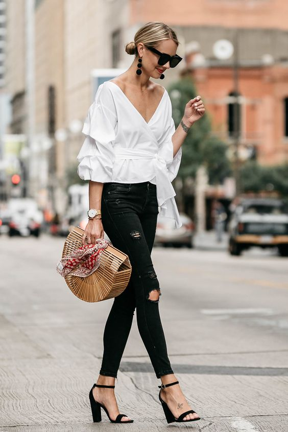 a white off the shoulder puff sleeve blouse, black ripped jeans, black block heels and a wooden bag