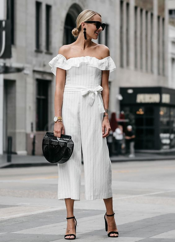 a white off the shoulder striped jumosuit with culottes, black minimalist block heels and a black bag