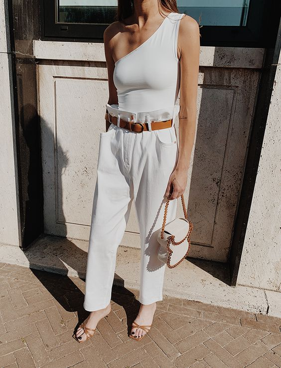 a white one shoulder top, white paperbag pants, a brown belt, brown heels and a white quirky bag