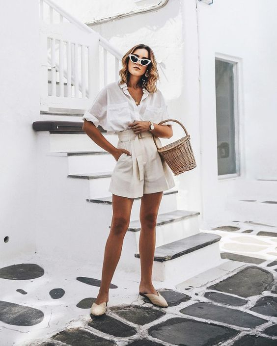 a white oversized shirt with short sleeves, neutral paperbag shorts, neutral mules and a basket