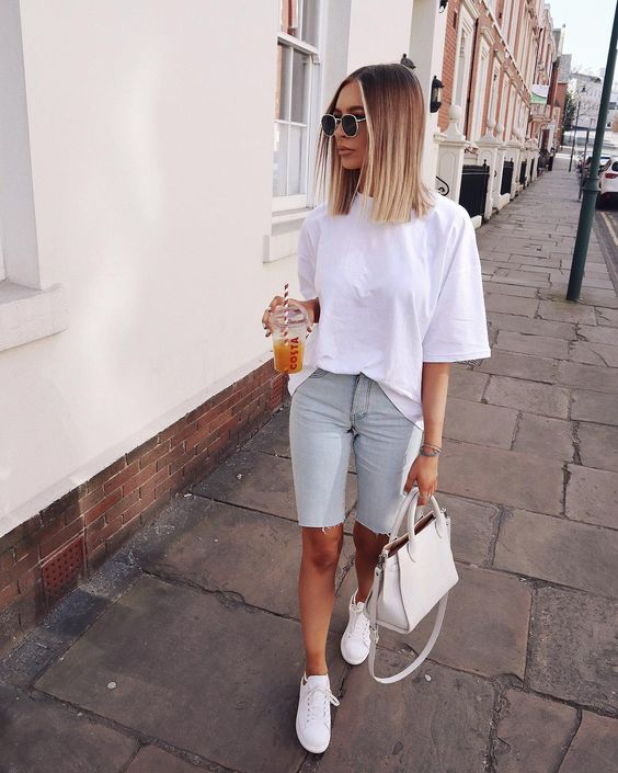 a white oversized tee, neutral denim cycling shorts, white sneakers and a white bag