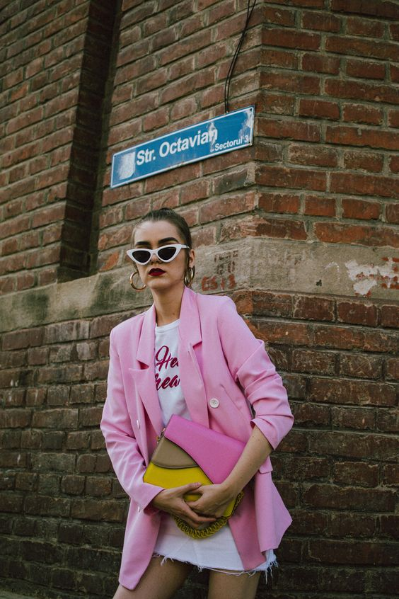 a white printed tee, a white denim skirt, a hot pink oversized blazer and a color block bag