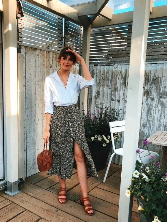 a white shirt, a black floral midi skirt on buttons, brown shoes and a basket bag