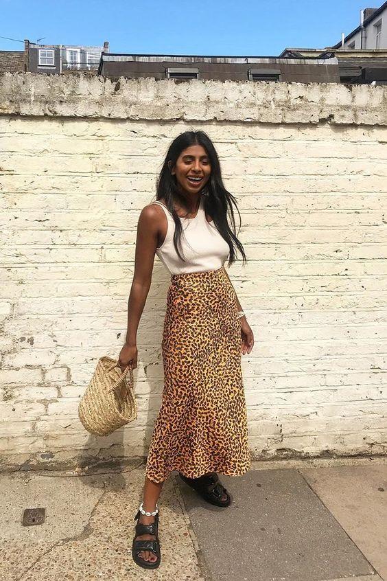 a white tank top, an animal print midi skirt, black sporty sandals and a woven bag