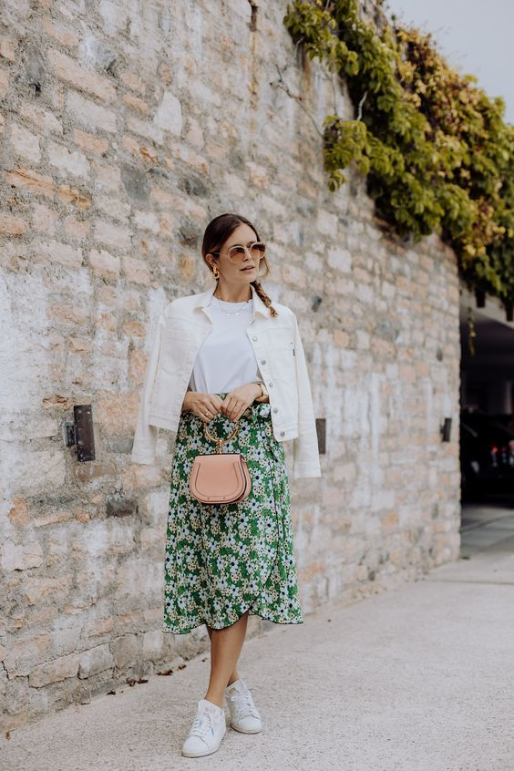 a white tee, a green floral wrap skirt, a white denim jacket, white sneakers and a blush bag