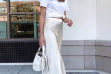 a white tied up tee, a neutral satin midi skirt, white sneakers and a white bucket bag for every day