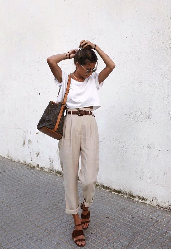 a wihte crop top, neutral high waisted pants, brown strappy shoes and a large black bag