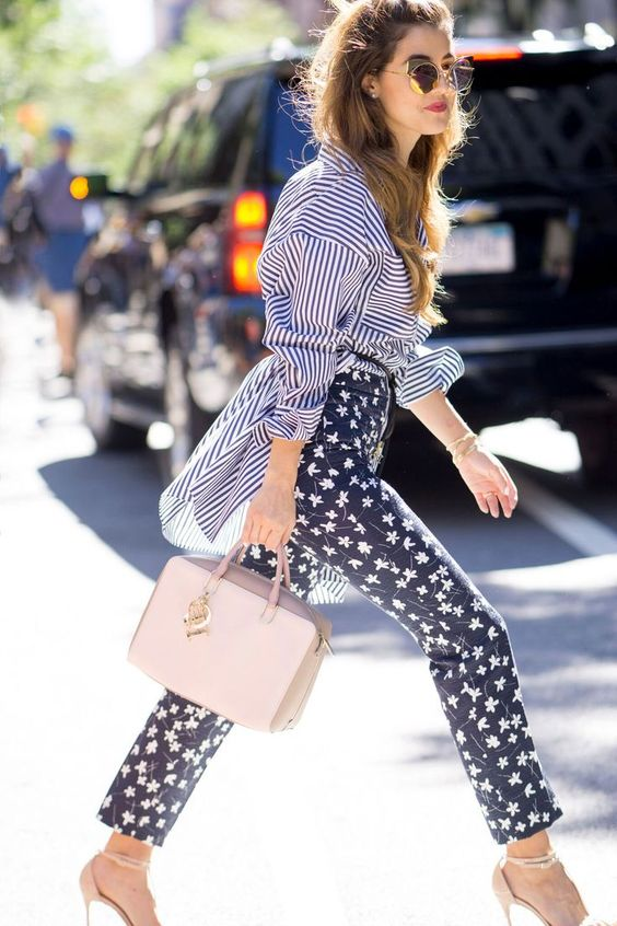 a work outfit with a striped oversized shirt, high waisted floral pants, nude heels and a blush bag