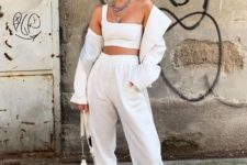 an all-neutral outfit with a one shoulder crop top, joggers, neutral trainers and a jacket