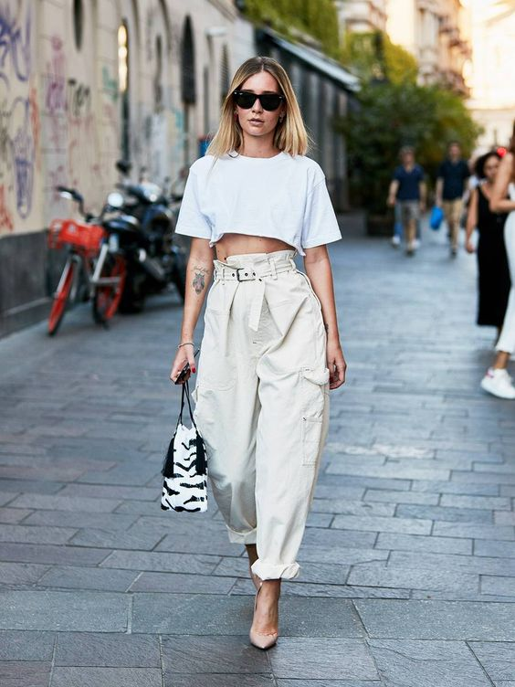 an edgy look with a white crop top, neutral baggy pants, blush heels and an animal print bag