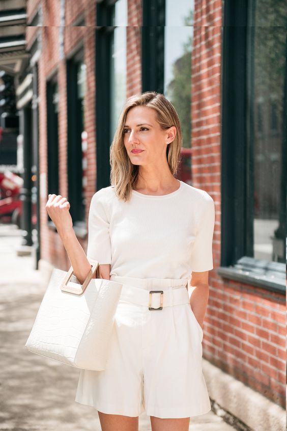an elegant all-white monochromatic look with a t-shirt, paperbag shorts and a tote