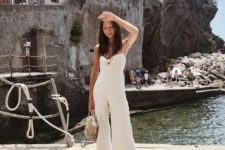 an off-white jumpsuit with a tied up bodice and wideleg cropped pants, sandals and a wicker bag