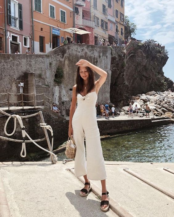 an off white jumpsuit with a tied up bodice and wideleg cropped pants, sandals and a wicker bag