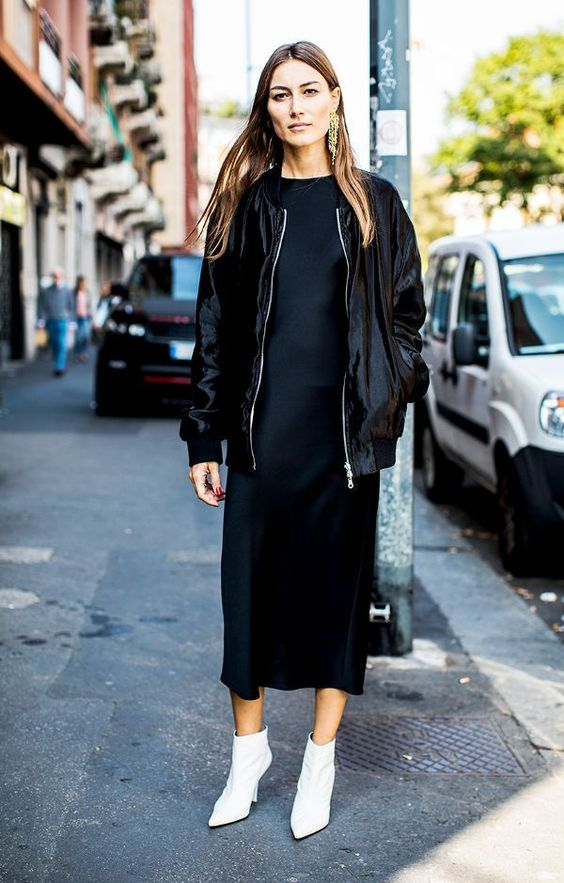 a silk black midi dress, a black bomber jacket, white booties and statement earrings