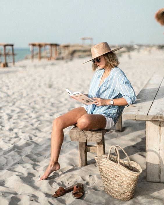 a beach look with an oversized striped shirt, white shorts, a straw hat and a straw bag plus brown leather slippers