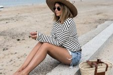04 a beachy outfit with a striped top, denim mini shorts, a wide brim straw hat and a straw bag, brown slippers