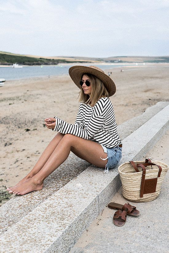 a beachy outfit with a striped top, denim mini shorts, a wide brim straw hat and a straw bag, brown slippers