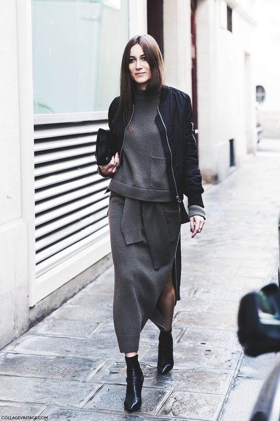 a grey sweatshirt and a matching midi skirt, black booties, a black bomber jacket and a clutch