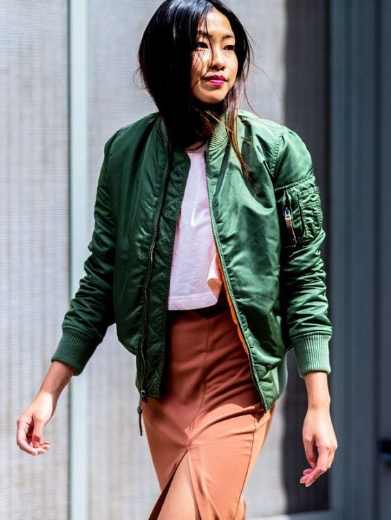 a white tee, a burnt orange skirt with a slit, a green bomber jacket for a bright fall outfit