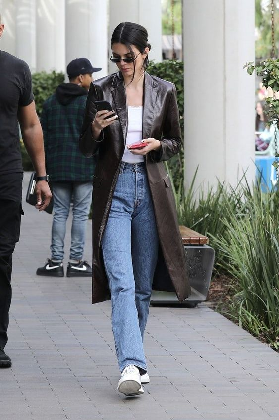 Kendall Jenner wearing a white top, blue jeans, white sneakers and a brown leather trench in 90s style