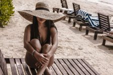 08 a black one piece swimsuit with an oversized floppy straw hat is a lovely tropical look