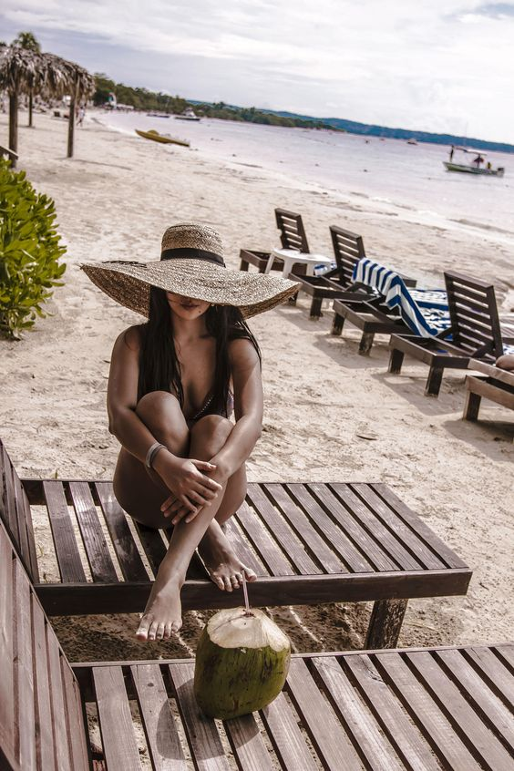 a black one piece swimsuit with an oversized floppy straw hat is a lovely tropical look