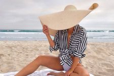09 a stylish beach look with a tied up striped shirt, a white swimsuit, an oversized straw hat