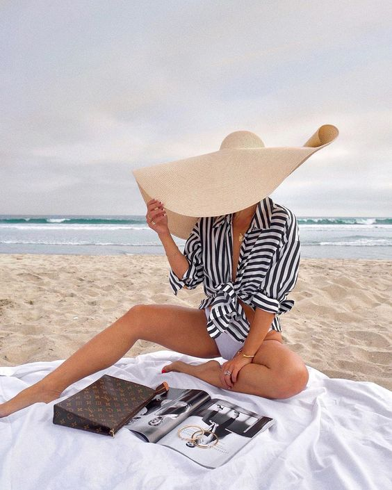 a stylish beach look with a tied up striped shirt, a white swimsuit, an oversized straw hat