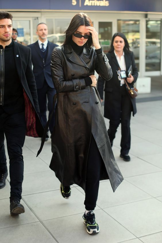 a total black look with a turtleneck, joggers, trainers, a leather trench by Kendall Jenner