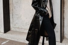 10 a fall to winter look with a neutral sweater, black pants, black boots, a lacquer leather trench