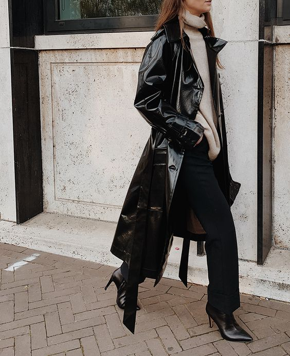 a fall to winter look with a neutral sweater, black pants, black boots, a lacquer leather trench