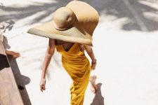 10 a refined vacation look with a bright yellow midi dress with a catchy neckline and an oversized hat